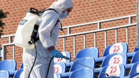 Un trabajador sanitario con equipo de protección rocía desinfectante en los asientos de la Plaza Roja antes del desfile.