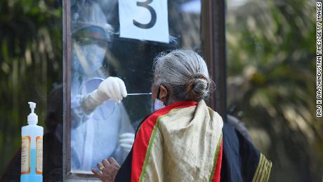 Un médico recoge un hisopo de una mujer para analizar Covid-19 el 18 de junio en Nueva Delhi, India.