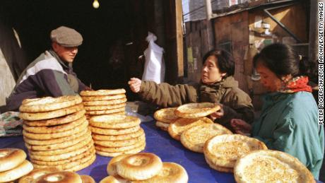Un hombre uigur vende pan plano tradicional a las mujeres que compran en la calle Xinjiang de Beijing en 1999.