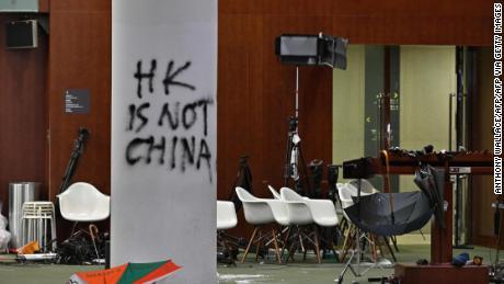 Se observan graffiti y sombrillas fuera de la cámara principal del Consejo Legislativo durante una gira de medios en Hong Kong el 3 de julio de 2019, dos días después de que los manifestantes irrumpieron en el complejo.