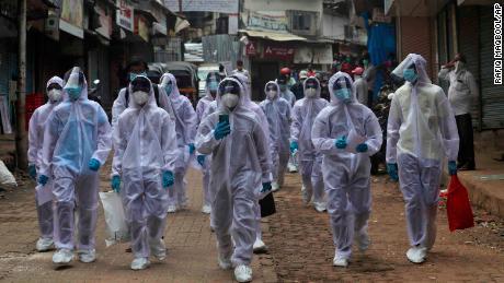 Los trabajadores de la salud llegan a un campamento médico en un barrio pobre de Mumbai, India, el 28 de junio.