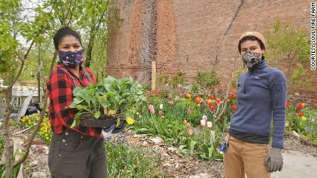 La directora asistente del programa Soul Fire Farm, Kiani Conley-Wilson, Left y Z Estime, construyen una cama de jardín para un miembro de la comunidad como parte del proyecto Soul Fire in the City.