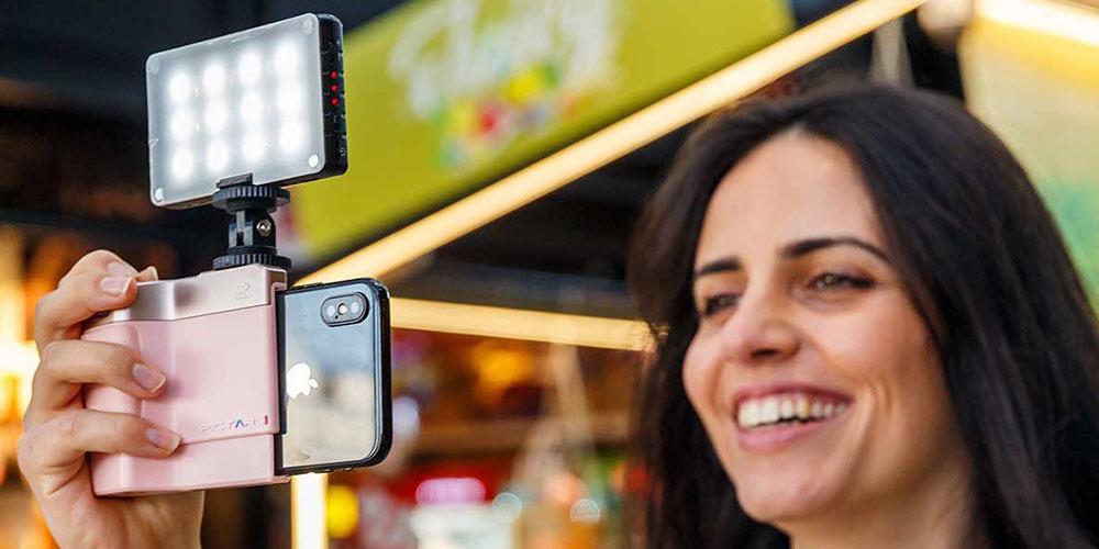 Una persona que toma una foto en su teléfono usando un accesorio de luz