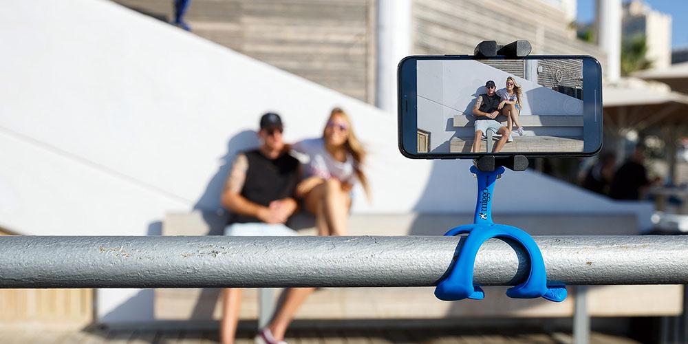 Un trípode que tiene un agarre flexible con un teléfono en primer plano, dos personas posando en segundo plano.