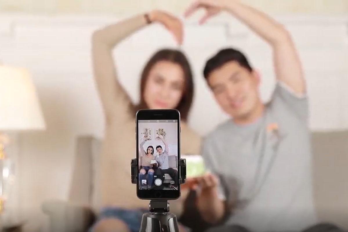 Un selfie stick en primer plano, con un teléfono tomando una foto de dos personas sentadas en un sofá con los brazos en forma de corazón