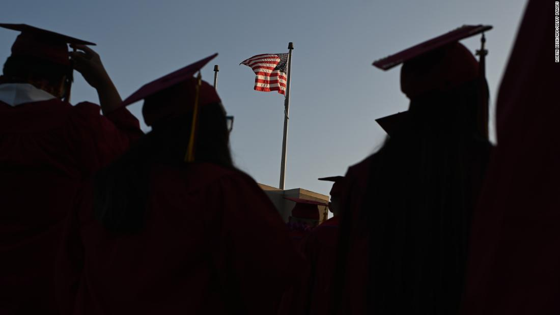 """A US flag flies above a building as students earning degrees at Pasadena City College participate in the graduation ceremony, June 14, 2019, in Pasadena, California. - With 45 million borrowers owing $1.5 trillion, the student debt crisis in the United States has exploded in recent years and has become a key electoral issue in the run-up to the 2020 presidential elections.""""Somebody who graduates from a public university this year is expected to have over $35,000 in student loan debt on average,"""" said Cody Hounanian, program director of Student Debt Crisis, a California NGO that assists students and is fighting for reforms. (Photo by Robyn Beck / AFP)        (Photo credit should read ROBYN BECK/AFP via Getty Images)"""