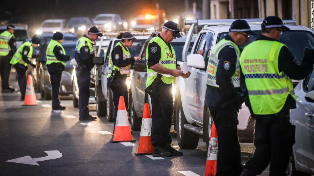 Police in the southern New South Wales (NSW) border city of Albury check cars crossing the state border from Victoria on July 7, 2020 as authorities close the border due to an outbreak of COVID-19 coronavirus in Victoria. - Australia on July 7 ordered millions of people locked down in its second-biggest city to combat a surge in coronavirus cases, as nations across the planet scrambled to stop the rampaging pandemic. (Photo by William WEST / AFP) (Photo by WILLIAM WEST/AFP via Getty Images)