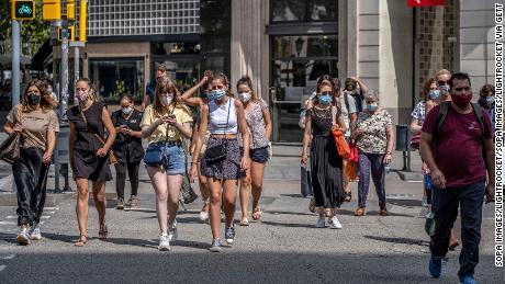 Las personas usan mascarillas en Barcelona, España, donde aquellos que no lo hacen en un espacio público enfrentan una multa de 100 euros.
