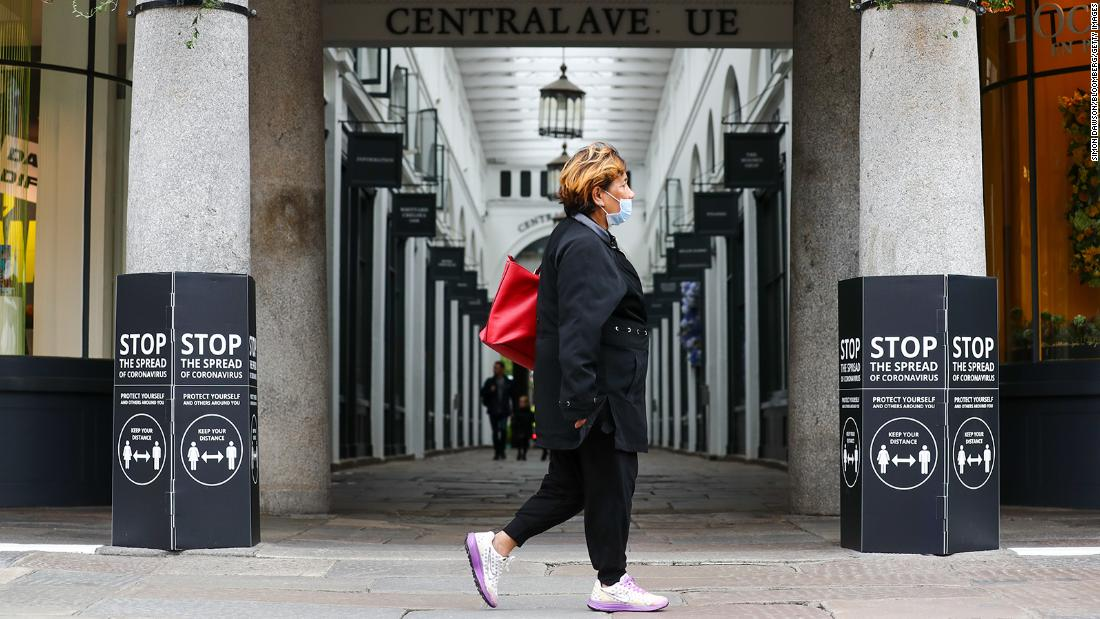 A pedestrian wearing a protective face mask passes an entrance to Covent Garden Market in London on Saturday, July 4. It is not mandatory to wear a mask in public places in England.