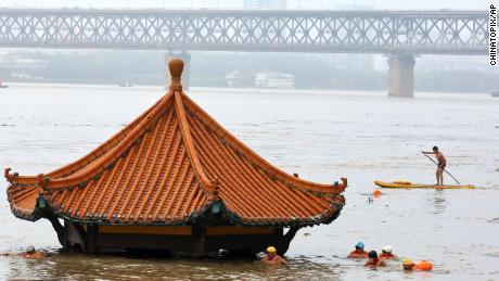 Los residentes nadan frente a un pabellón junto al río sumergido por el río Yangtze inundado en Wuhan, en la provincia de Hubei, en el centro de China, el 8 de julio.