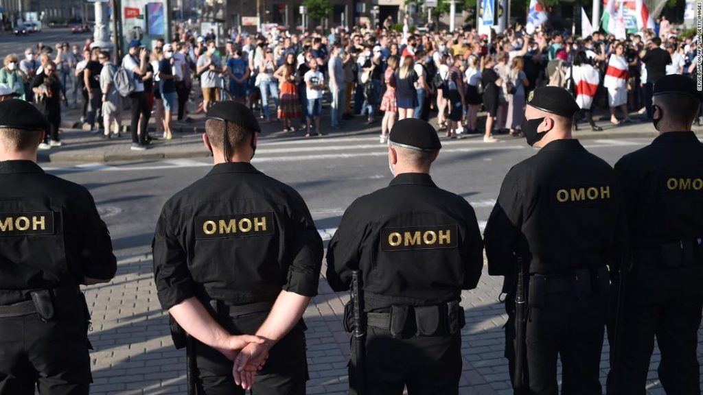 Belarus' riot police officers watch opposition supporters during a gathering to support candidates seeking to challenge President Alexander Lukashenko in August's polls in Minsk on June 19, 2020.