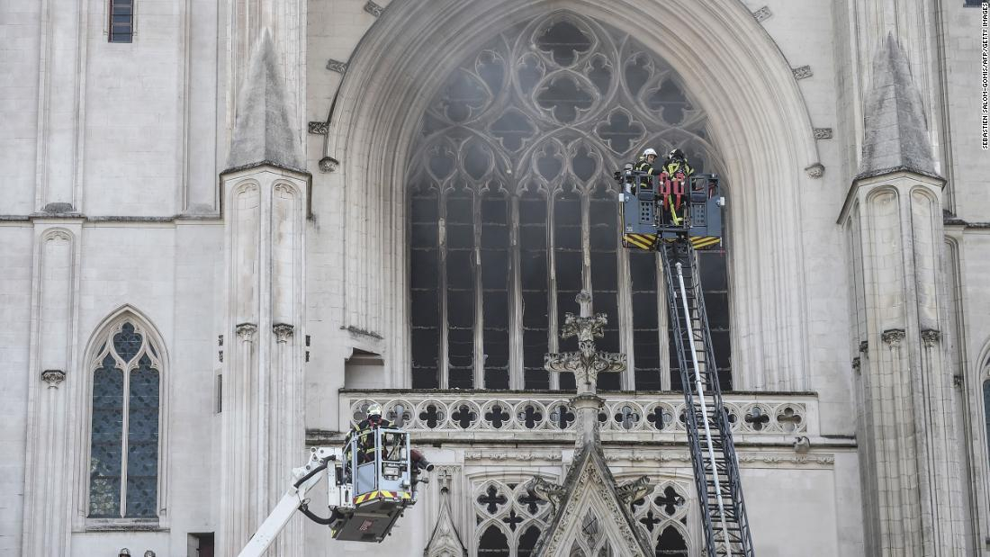 Smoke billows from the front windows of the soaring Gothic structure.
