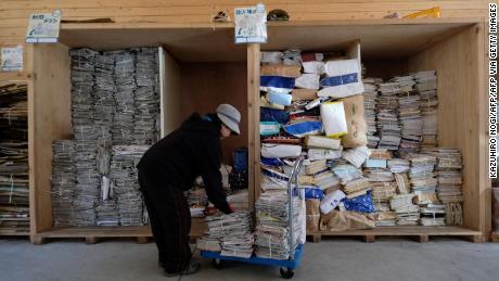 Un trabajador clasifica periódicos y revistas para reciclar en un centro de residuos en Kamikatsu.