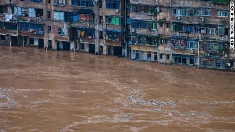 Las aguas de la inundación fluyen más allá de un edificio residencial en Chongqing, en el suroeste de China, el 1 de julio.