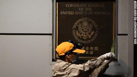 Un trabajador intenta quitar una placa en la pared afuera del Consulado de los Estados Unidos en Chengdu, suroeste de China.