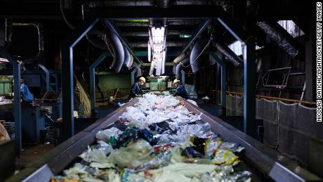 Los trabajadores clasifican los residuos plásticos desechables en una cinta transportadora en el centro de reciclaje Ichikawa Kankyo Engineering. La oficina de la ciudad de Katsushika de Tokio trae diariamente unas 10 toneladas de recursos reciclables de plástico a las instalaciones de reciclaje.