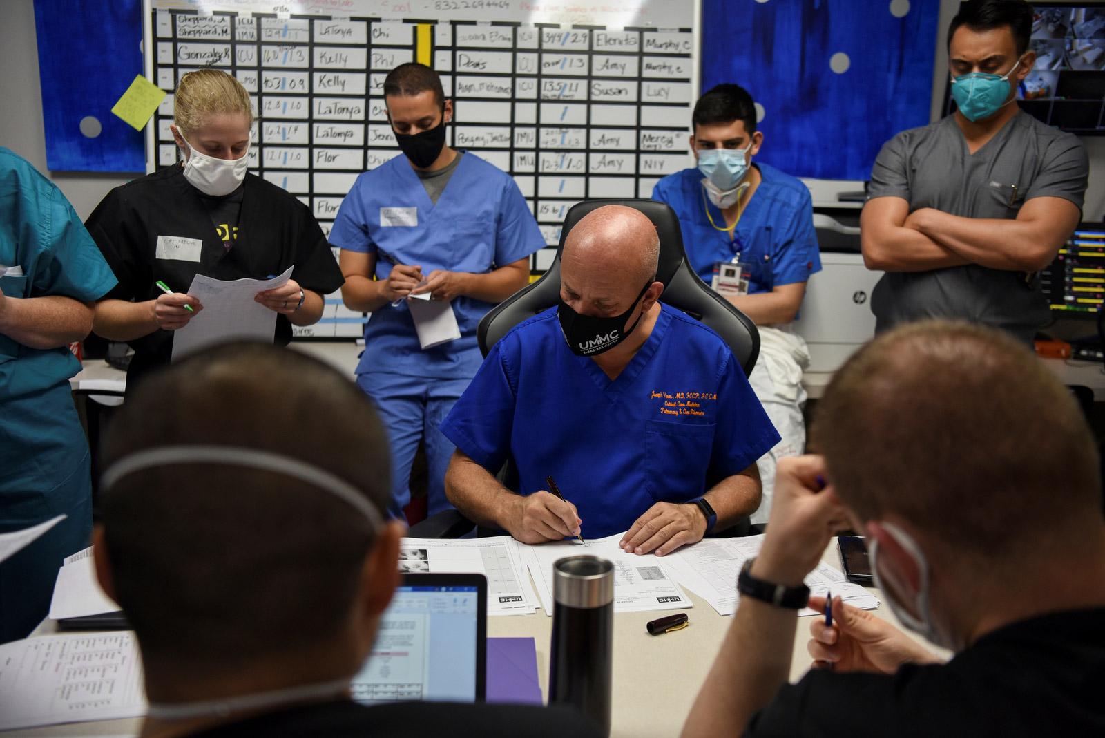 Varon y su equipo revisan los archivos de los pacientes durante una reunión diaria.