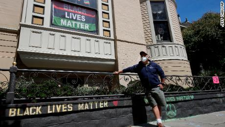 James Juanillo posa con un mensaje escrito con tiza fuera de su casa en San Francisco, California, el 14 de junio de 2020.