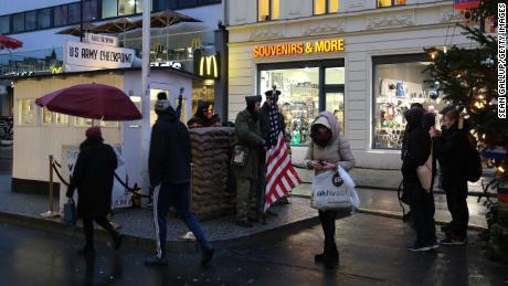 Los turistas toman fotos de actores vestidos como soldados en el ex Checkpoint Charlie en Berlín, donde los tanques estadounidenses y soviéticos se enfrentaron en los primeros años de la Guerra Fría.