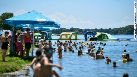 Las cosas están volviendo a la normalidad en Italia.  La gente nada en un lago artificial en Milán, el 12 de julio.