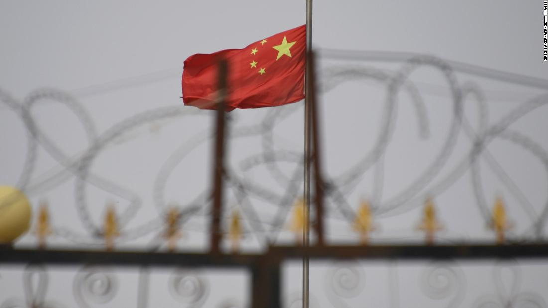 TOPSHOT - This photo taken on June 4, 2019 shows the Chinese flag behind razor wire at a housing compound in Yangisar, south of Kashgar, in China's western Xinjiang region. ( Photo by GREG BAKER/AFP/Getty Images)