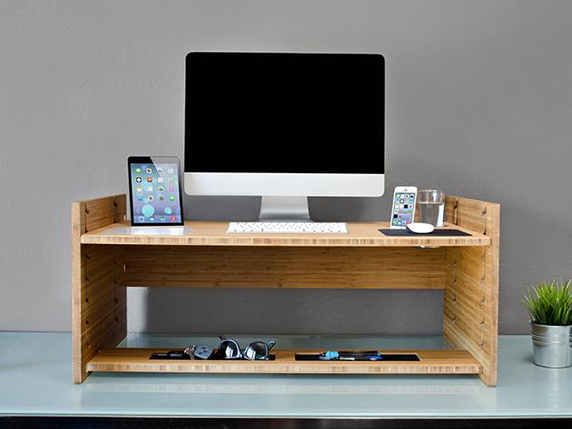 Un escritorio con un estante de escritorio de pie y otros dispositivos electrónicos personales