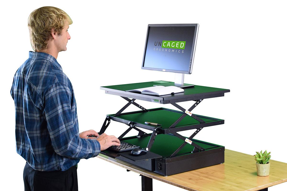 Una persona que trabaja desde un escritorio de pie ajustable.