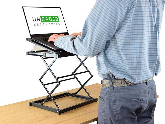 Una persona que trabaja en un convertidor de escritorio de pie.
