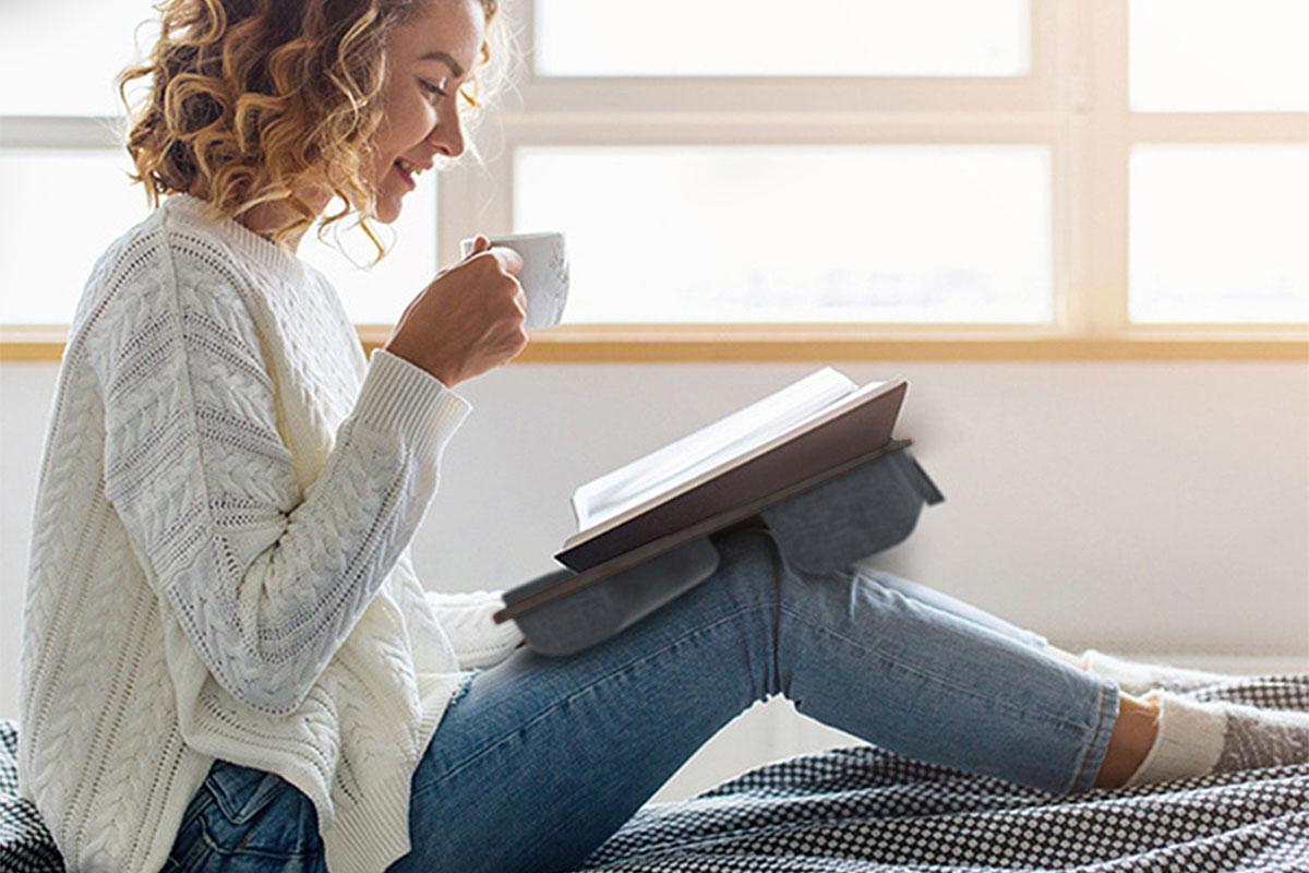 Una persona que trabaja desde la cama con un escritorio portátil en su regazo.