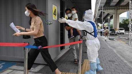 Un funcionario de salud con equipo de protección guía a los visitantes en una estación de pruebas de coronavirus Covid-19 en Seúl el 18 de agosto de 2020.