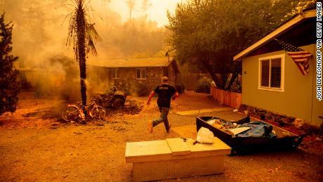 Un residente corre a una casa para salvar a un perro mientras las llamas se acercan mientras un incendio se desata el martes cerca del lago Berryessa cerca de Napa.