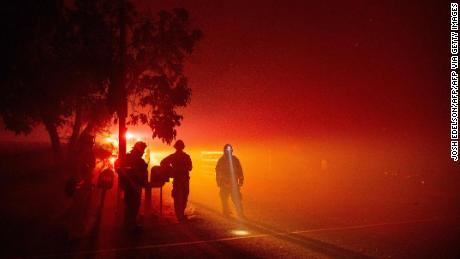 Los bomberos vigilan las llamas cuando se acercan a una casa en Vacaville, California.