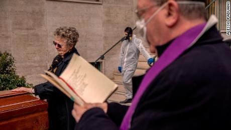 Un sacerdote con una máscara bendice un ataúd dentro del patio de un edificio en Nápoles, Italia, el 27 de marzo.