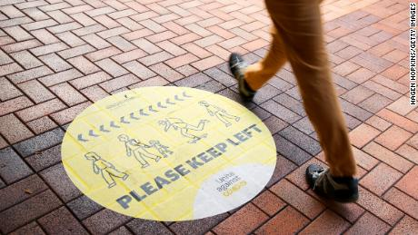 Un peatón pasa junto a un letrero de distanciamiento social el 14 de agosto de 2020 en Wellington, Nueva Zelanda.