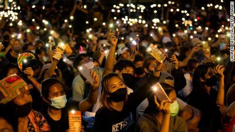 Estudiantes y manifestantes antigubernamentales encienden sus teléfonos en el Monumento a la Democracia el 16 de agosto de 2020 en Bangkok.